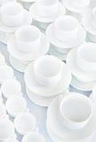 Le tazze bianche si levano in piedi in una riga su una tabella Immagine Stock Libera da Diritti