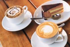 Le tazze del caffè del cappuccino e della mousse di cioccolato caldi agglutinano Immagine Stock Libera da Diritti