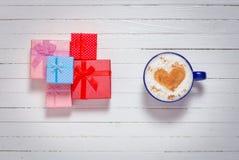 Le tazze di caffè con cuore modellano il simbolo ed i contenitori di regalo Fotografie Stock