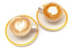Le tazze di caffè del cuore di arte del latte modellano su fondo bianco isolato Immagini Stock