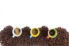 Le tazze di caffè variopinte hanno allineato sui chicchi di caffè isolati su bianco Fotografia Stock Libera da Diritti