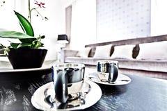 Le tazze di tè brillanti del metallo si chiudono su su una tavola nera fotografia stock