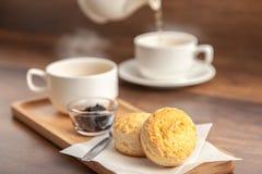 Le tazze di tè sono servito con le focaccine al latte e l'inceppamento casalingo del mirtillo sopra corteggia Fotografia Stock