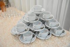 Le tazze ed i piattini bianchi con i cucchiai sono su a vicenda sotto forma di una piramide Immagini Stock