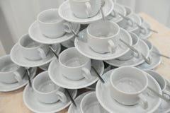 Le tazze ed i piattini bianchi con i cucchiai sono su a vicenda sotto forma di una piramide Fotografia Stock