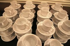 Le tazze ed i piattini bianchi sono impilati sul livello Fotografia Stock Libera da Diritti