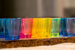 Le tazze gialle, blu, rosse per i cocktail hanno allineato accanto a ogni altro su una superficie di legno Immagini Stock