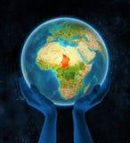 Le Tchad sur terre dans des mains dans l'espace illustration libre de droits
