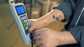 le technicien Artificiel-remis d'atelier règle un à télécommande d'un dispositif de fraisage banque de vidéos