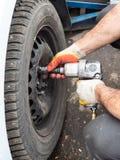 Le technicien attache la roue de voiture par la clé pneumatique photo libre de droits