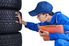 Le technicien avec l'uniforme bleu vérifie des pneus Photographie stock libre de droits