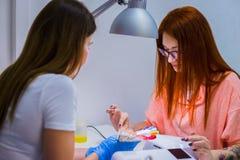 Le technicien de clou montre la palette de couleurs des services de clou dans le beau Photographie stock libre de droits