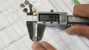 Le technicien de plan rapproché mesure de petites parties avec le multimètre numérique banque de vidéos