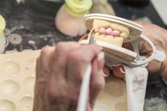 Le technicien dentaire Applying Porcelain To 3D a imprimé le moule d'implant Photos stock