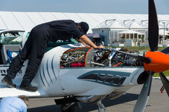 Le technicien inspecte la formation biplace et les avions à voilure basse acrobatiques aériens Grob G 120TP de turbopropulseur Photo libre de droits