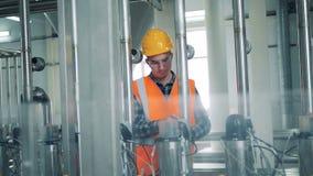 Le technicien masculin règle la pression dans l'équipement de brassage banque de vidéos