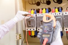 Le technicien mesure la tension ou le courant par le voltmètre dans le contr photos stock