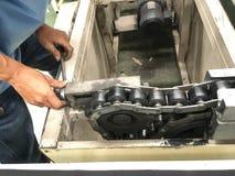 Le technicien réparant la bande de conveyeur dans l'usine Photographie stock libre de droits
