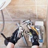 Le technicien sanitaire répare le piège de tuyauterie photographie stock