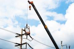 Le technicien travaille dans un seau haut sur un poteau de puissance Photos stock
