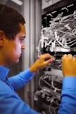 Le technicien vérifiant des câbles dans un support a monté le serveur image libre de droits