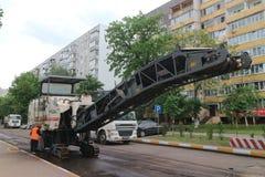 Le tecniche della strada effettua la riparazione di una copertura della strada nella via Immagine Stock Libera da Diritti