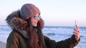 Le tecnologie di Internet, giovane donna in vetri con lo smartphone in mani comunica con gli amici sull'oceano stock footage