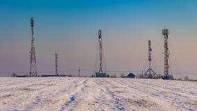 le Telecomunicazioni trasmettono su un campo nevoso visto nell'inverno fotografia stock libera da diritti