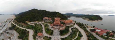 Le temple rouge de toit est situé à mi-chemin vers le haut de la montagne verte image stock