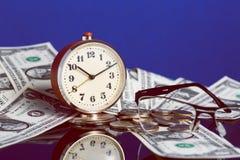 Le temps, c'est de l'argent concept avec la vieille horloge de vintage, les billets d'un dollar, les lunettes et la réflexion gen Photo libre de droits