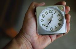 Le temps, c'est de l'argent concept - horloge en main Photos stock