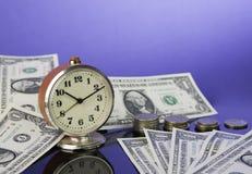 Le temps, c'est de l'argent, horloge de vintage sur les billets d'un dollar américains d'argent liquide et pièces avec le fond bl Photographie stock libre de droits