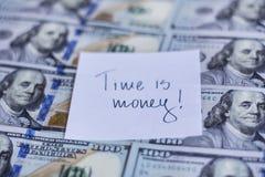 Le temps, c'est de l'argent note sur un fond de billets d'un dollar Photo libre de droits
