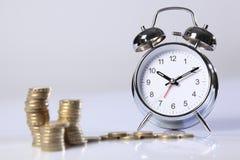 Le temps, c'est de l'argent pièces de monnaie de livre argentées d'horloge et d'or Images libres de droits