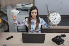 Le temps, c'est de l'argent, selon la femme d'affaires Photographie stock libre de droits