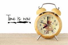 Le temps est maintenant des mots sur le mur et l'horloge blancs de vintage Images libres de droits
