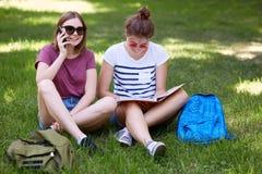 Le tenager femelle adorable joyeux parle par l'intermédiaire du téléphone intelligent se repose près de son ami de ballot qui lit Photographie stock
