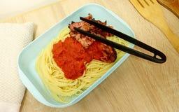 Le tenaglie di plastica si trovano sopra un contenitore di alimento di plastica imballato con gli spaghetti, la salsa al pomodoro immagine stock libera da diritti