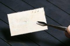 le tenaglie tengono il francobollo con il lato posteriore inutilizzato fotografia stock libera da diritti