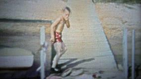 LE TENNESSEE, ETATS-UNIS - 1954 : L'enfant fait l'éclaboussure de piqué de canonball au trou de natation d'été banque de vidéos