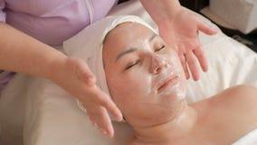 Le tenute dell'estetista consegna il fronte di una donna asiatica senza toccare la pelle Servizio di VIP nel centro di cosmetolog