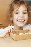 Le tenute della bambina aprono la scatola di cartone ondulato con i biscotti Fotografia Stock