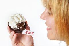 Le tenute della giovane donna agglutinano l'agnello come il simbol 2015 nuovi anni ha isolato Immagine Stock Libera da Diritti