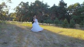 Le tenute felici dello sposo dentro arma la sua sposa stock footage