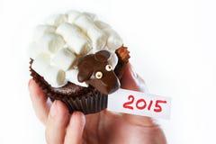 Le tenute femminili della mano agglutinano l'agnello come il simbol 2015 nuovi anni ha isolato Immagine Stock