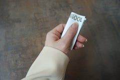 Le tenute femminili della mano hanno piegato la banconota di valuta Immagini Stock