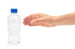 Le tenute femminili della mano puliscono ed acqua dolce imballata in una bottiglia di plastica Isolato su priorità bassa bianca Fotografie Stock Libere da Diritti