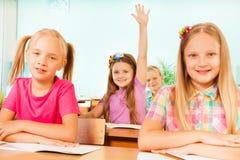 Le tenute sorridenti della ragazza armano su dietro due ragazze Fotografia Stock