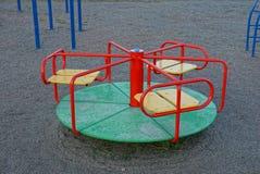 Le terrain de jeu des enfants avec un rond a coloré le carrousel au sol dans la rue photographie stock