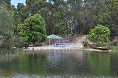 Le terrain de jeu des enfants colorés près d'un lac dans le pays Photos stock